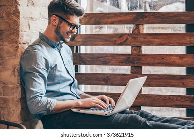 Blogger at work.Side view of handsome young man working on laptop and smiling while sitting at windowsill