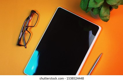 Blogger`s mockup. Flat lay workspace with a tablet ,pen and glasses on a bright colorful background