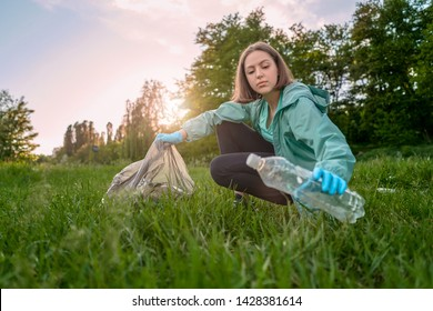 Blogging concept. The girl collects trash from the forest in the trash bag