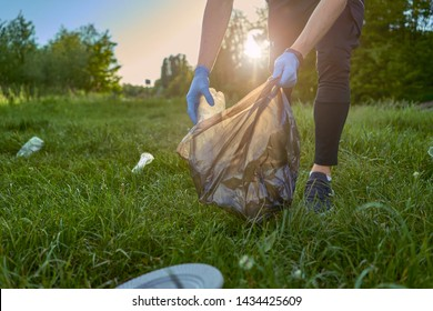 Blogging concept. A man collects trash from the forest in the trash bag
