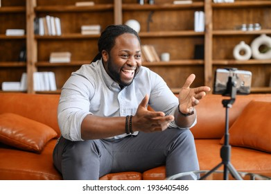 Blogging concept. Young African American male blogger in casual clothes streaming video online or recording tutorial for social media network, looking at the mobile phone on a tripod and laughing