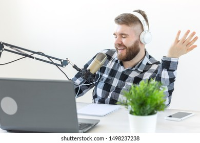 Blogging, music and broadcasting concept - young male dj at radio studio