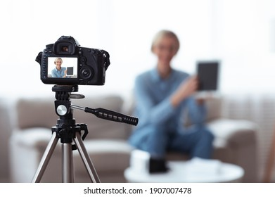Blogging and social media marketing concept. Millennial female influencer recording video content for her blog, advertising new touch pad. Focus on camera with preview screen, copy space
