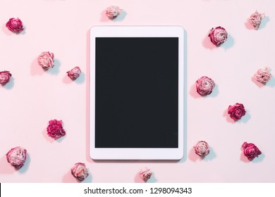 Blogging and social networks. Tablet computer with black screen on pink rose background. Flat lay.