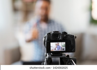 blogging, videoblog and people concept - camera recording video blog of indian male blogger showing thumbs up at home