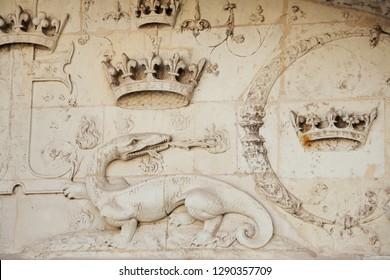 BLOIS, FRANCE - JULY 15, 2018: Royal Chateau de Blois (Royal Castle of Blois). Architectural detail of building exterior. Fire breathing Salamander with crowns - emblem of Francois I.