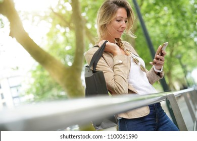 Blond attractive woman on shopping day using smartphone