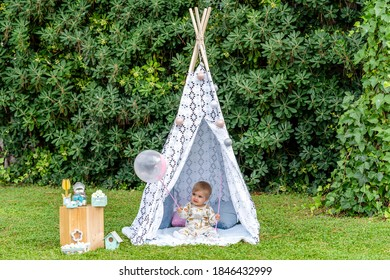 blond baby with blue eyes of a few months playing with a balloon sitting in a teepee tent