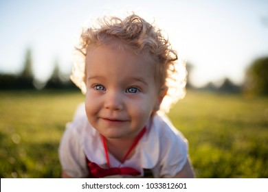 blond baby with blue eyes sitting in the grass of a park on a sunny afternoon