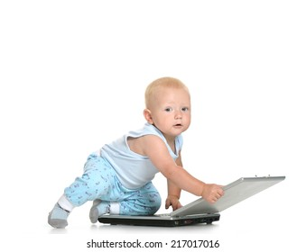 Blond baby boy playing with laptop on a white background