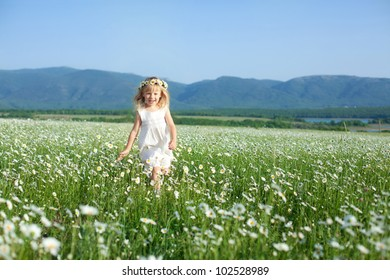 Blond baby girl in wreath running in field of camomiles