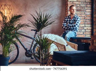 A blond bearded hipster male dressed in a fleece shirt and jeans posing in a room with loft interior.