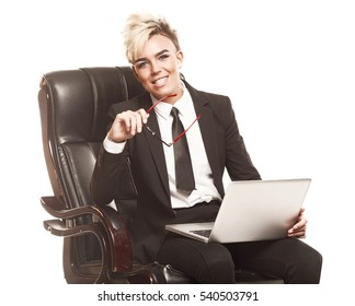 Blond beautiful business lady in white shirt eyeglasses black suit and black tie sit on chair
