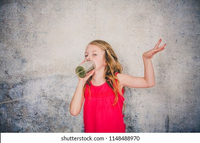 blond, beautiful Girl is on the phone with a corded phone made out of a can
