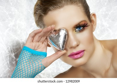 Blond beautiful woman with blue eyes and fashion make-up holding a silver heart, wearing blue fingerless gloves. Not isolated