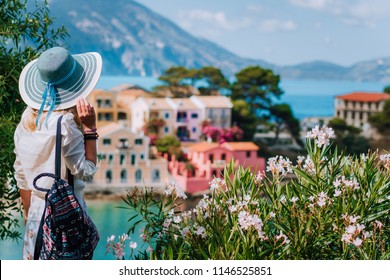 Blond beautiful woman in blue sun hat and white clothes enjoying view of colorful tranquil village Assos houses on sunny day. Stylish female visiting Kefalonia in summer time on Greece travel vacation