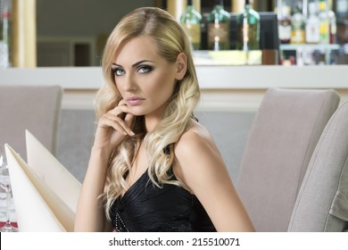 blond beautiful woman sitting at restaurant . very elegant , waiting for someone . looking in camera