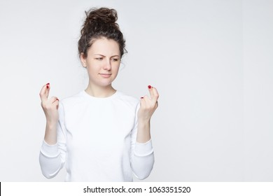 Blond beautiful young female learning how to make mudra sign, try to relax after hard working day, to practice yoga against wall background. Young pretty woman meditates indoor. Relaxation concept.