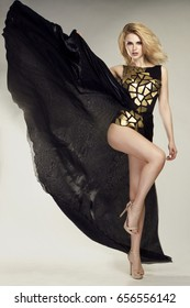 Blond beauty  in gorgeous fashionable black long evening dress, looking at the camera
