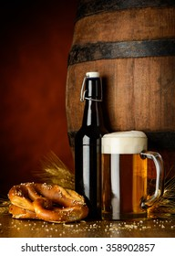 Blond beer in a bottle, mug and a pretzel on a wooden table with wheath and a rustic barrel