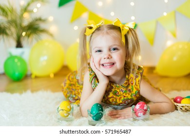 blond, blue-eyed pretty girl  child smiling ponytail hair in yellow dress 4-5 years with Easter eggs in a room on the background of yellow decoration, lying on his stomach, studio