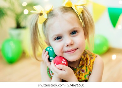 blond, blue-eyed pretty girl smiling ponytail hair in yellow dress 4-5 years with Easter eggs in a room on the background of yellow design studio