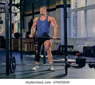 Blond bodybuilder with broken leg in bandage holds cross fit hammer in a gym club.