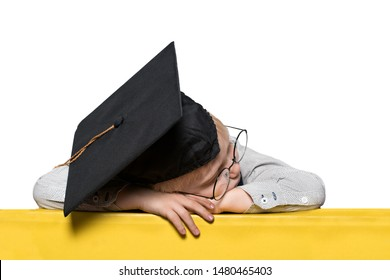 Blond boy in an academic hat and glasses asleep on the table. Isolate. School concept
