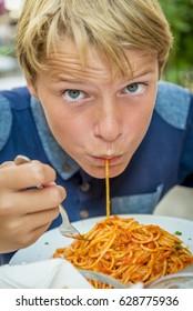 blond boy with blue eyes eating spaghetti