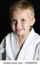 Blond boy with blue eyes in karate uniform