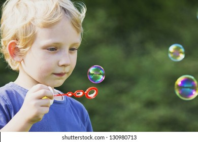 Blond boy in blue shirt blows  bubbles in the garden.
