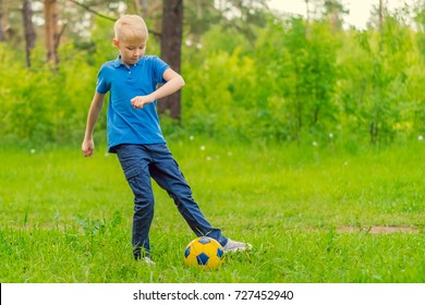 Blond boy in a blue T-shirt playing football in the park
