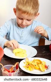 Blond boy child kid preschooler peeling fruit apple eating cooking at home. Happy childhood.