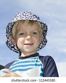 Blond boy in a hat looking at the camera