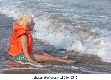 Blond boy in an inflatable swimming vest sits on seashore in the water