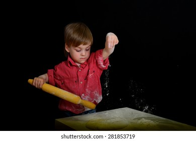 Blond boy kneads dough smeared with flour. On a black background
