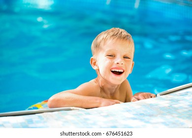 The blond boy laughs. The boy on the side of the pool is smiling.