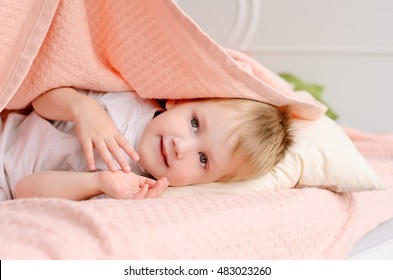 blond boy lying on a bed under a pink blanket on a white pillow