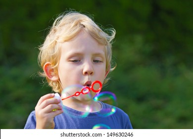 Blond boy making soap bubbles outside (green background)