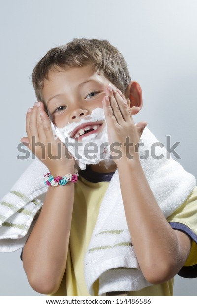Blond boy with missing tooth smile while placing shaving cream with both hands