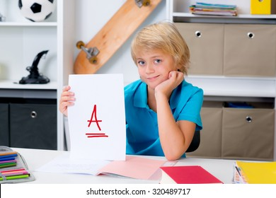 blond boy on desk with good report card