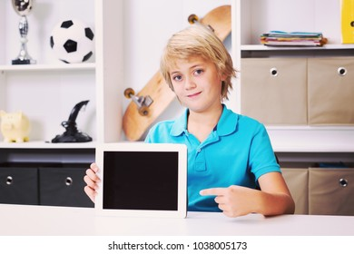 blond boy pointing of his tablet computer