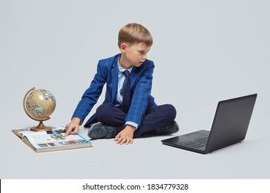 blond boy in a school suit is sitting in front of a laptop, a globe, and a book. photo session in the Studio on a white background