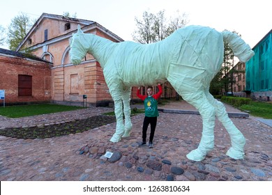 Blond boy under horse sculpture in Mark Rothko Art Centre near Artillery arsenal in Daugavpils Fortress, (Dinaburg Fortress) is an early 19th century fortress in Daugavpils, Latvia -  July, 2018.