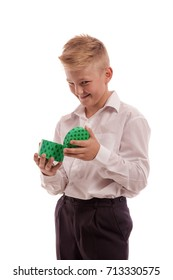 Blond boy in a white shirt with a green box with a gift in hands posing on a white background