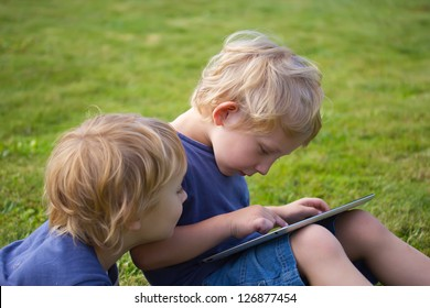 The blond boys (brothers) are playing with the PC tablet outdoor.