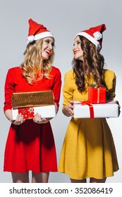 Blond and brunette beautiful smiling girls wearing red santa claus hats and holding gift boxes are celebrating christmas and new year on white isolated background. Party concept