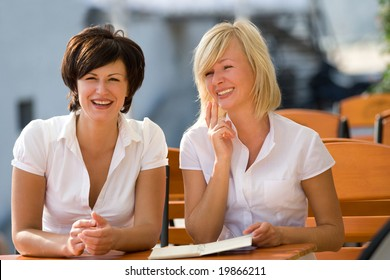 Blond and brunette girls sitting in coffee house at sunny day