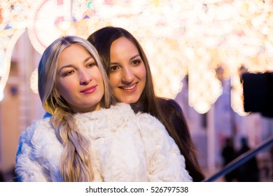 Blond and brunette sisters using selfie stick taking pic on on a night street with Christmas light decorations. Friendship, love and travel concept. Girls in trend