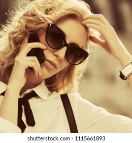 Blond business woman in sunglasses calling on cell phone in city street Stylish fashion model wearing white shirt and necktie outdoor